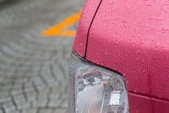 一辆红色汽车的车灯有雨珠的 库存图片