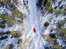 一辆红色汽车的鸟瞰图在白色冬天路的 冬天风景乡下 多雪的森林航拍有一辆汽车的在 免版税库存照片