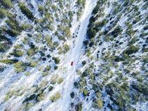 一辆红色汽车的鸟瞰图在白色冬天路的 冬天风景乡下 多雪的森林航拍有一辆汽车的在 免版税库存图片