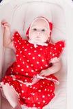 一辆红色礼服婴儿推车的小女孩 免版税库存照片