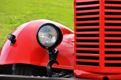 一辆红色葡萄酒汽车的前面零件有被弄脏的绿叶背景 库存照片