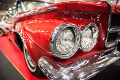 一辆红色葡萄酒汽车的车灯 免版税库存照片