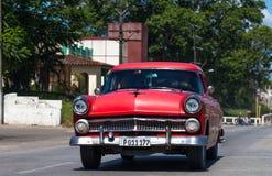 一辆红色经典汽车在街道上drived在哈瓦那市 免版税库存图片