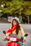 一辆红色滑行车的可爱的愉快的妇女 免版税图库摄影