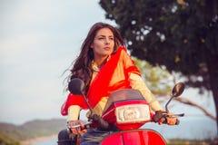 一辆红色滑行车的可爱的愉快的妇女 免版税库存图片