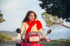 一辆红色滑行车的可爱的愉快的妇女 库存照片