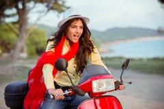 一辆红色滑行车的可爱的愉快的妇女 图库摄影