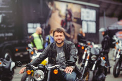 一辆经典摩托车的人在城市,没有盔甲的一件黑夹克的,驾驶安全 库存图片