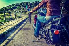 一辆经典摩托车的女孩 免版税库存照片