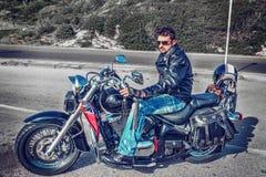 一辆经典摩托车的骑自行车的人 库存图片