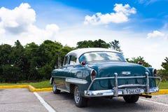 一辆美丽的经典汽车在古巴在蓝天下 免版税库存照片