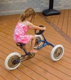 一辆老三轮车的一个小女孩 免版税图库摄影