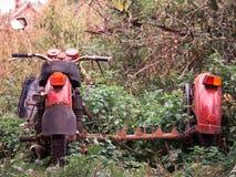 一辆老和被放弃的红色摩托车的被定调子的图象 免版税图库摄影