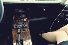 一辆老在位子的汽车,电子和妇女的脚的内部 库存照片