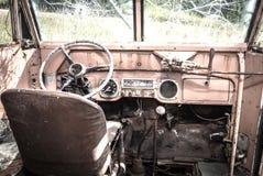 一辆老失败的古色古香的公共汽车的前面内部 免版税库存图片