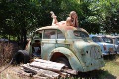 从一辆老打破的汽车的沉思国家女孩 免版税库存图片