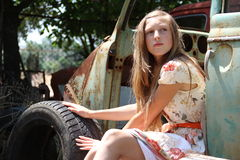 从一辆老打破的汽车的沉思国家女孩 库存照片