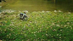 一辆老摩托车停放反对河边 免版税图库摄影