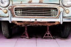 一辆老汽车的前面的细节在车库的 免版税库存照片