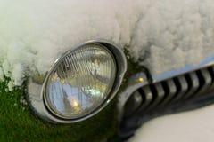 一辆老汽车的前面车灯在冬天 长满的青苔 降雪 免版税图库摄影