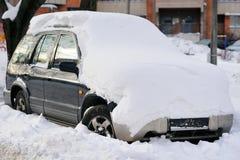 一辆老汽车的前面车灯在冬天 降雪 免版税库存照片