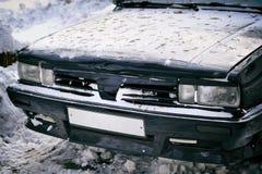 一辆老汽车的前面车灯在冬天 库存图片