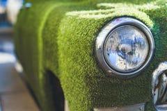 一辆老汽车的前面车灯在用人为草包括的夏天 装饰在古典汽车 免版税图库摄影