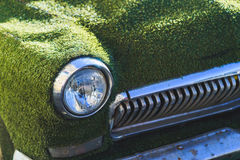 一辆老汽车的前面车灯在用人为草包括的夏天 装饰在古典汽车 免版税库存图片