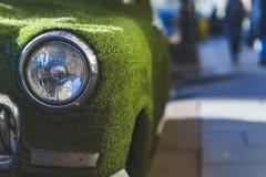 一辆老汽车的前面车灯在用人为草包括的夏天 装饰在古典汽车 库存照片