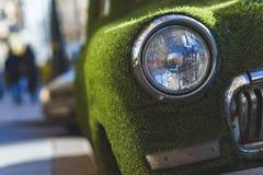 一辆老汽车的前面车灯在用人为草包括的夏天 装饰在古典汽车 图库摄影