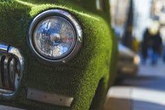 一辆老汽车的前面车灯在用人为草包括的夏天 装饰在古典汽车 库存图片
