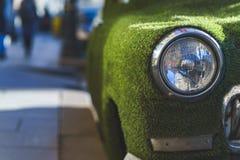 一辆老汽车的前面车灯在用人为草包括的夏天 装饰在古典汽车 免版税库存照片