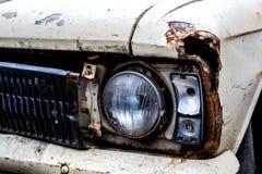 一辆老汽车的前面车灯的细节在车库的 免版税库存照片