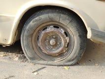 一辆老汽车的残破的轮子 免版税库存照片