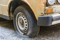一辆老汽车的泄了气的轮胎在路的 图库摄影