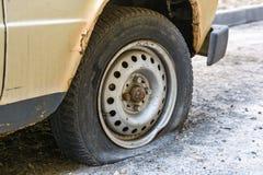 一辆老汽车的泄了气的轮胎在路的 免版税库存图片