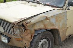 一辆老生锈的残破的汽车的前面部分的片段在事故 免版税图库摄影