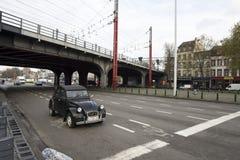 一辆老甲虫汽车作为在一个交叉点的唯一的汽车在有南火车站的火车桥梁的布鲁塞尔 免版税库存照片