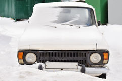 一辆老白色汽车的前面车灯在冬天 降雪 免版税图库摄影