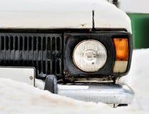 一辆老白色汽车的前面车灯在冬天 降雪 免版税库存照片