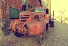 一辆老红色卡车的生锈的格栅在街道减速火箭的老汽车停放了 免版税库存图片