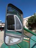 一辆老绿色生锈的葡萄酒公共汽车的侧面窗在一个正方形停放的后视镜反射了在一个村庄在塞浦路斯 免版税库存照片
