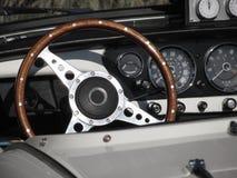 一辆老英国经典汽车的仪表板 方向盘和车仪表盘特殊看法  汽车是胜利TR 免版税图库摄影