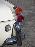一辆老英国经典汽车的后方 正确的尾巴光和发光的镀铬物防撞器特殊看法  汽车是胜利TR3模型 免版税库存照片