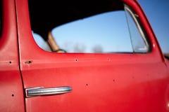 一辆老葡萄酒红色汽车的侧面窗 免版税库存照片