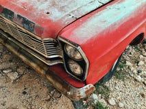 一辆老葡萄酒红色汽车的前面 库存照片