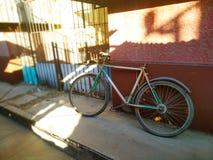 一辆老葡萄酒自行车在破旧的老墙壁附近站立 免版税图库摄影