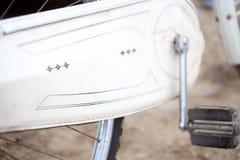 一辆老蓝色葡萄酒减速火箭的自行车和链嵌齿轮的特写镜头有脚蹬的反对 库存照片
