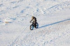 一辆肥胖自行车的骑自行车者沿冻冬天海乘坐在海滩 免版税图库摄影