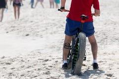 一辆肥胖轮子自行车的一个人在海滩 图库摄影